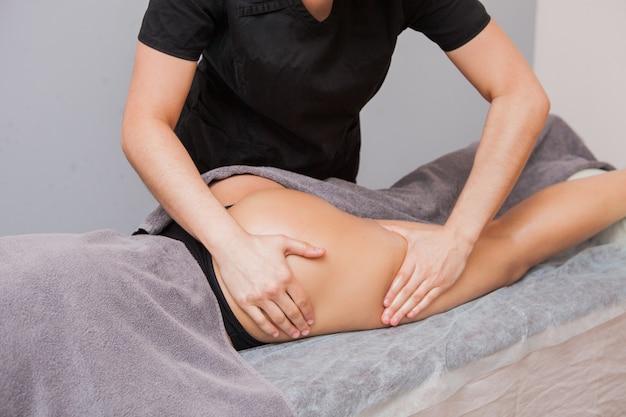 Женский массажист делает антицеллюлитный массаж молодой женщины крупным планом