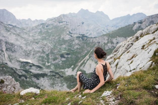 山の谷を探して山の上に座っているきれいなドレスの若い女性