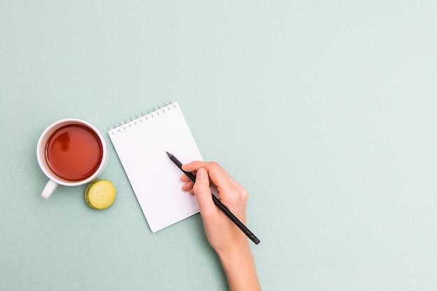 デスクで空白のメモ帳に書く女性の手の平面図です。青いテーブルにお茶とマカロンのカップを置きました。