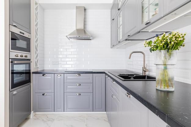 Интерьер современной кухни. темная столешница и раковина, серые фасады шкафчиков. ваза с цветами украшает стол