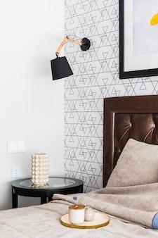 Красивый интерьер спальни. дорогая удобная кровать с высоким изголовьем, декор на журнальном столике. на настенный светильник и рамка для картинки