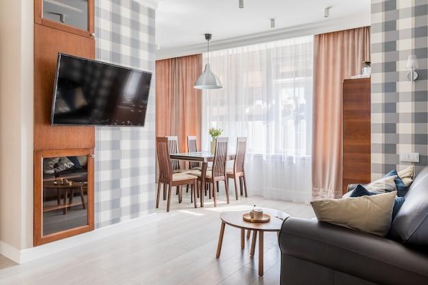 Интерьер гостиной и кухни с диваном, телевизором и большим окном за занавесками. есть обои в клетке на стенах.