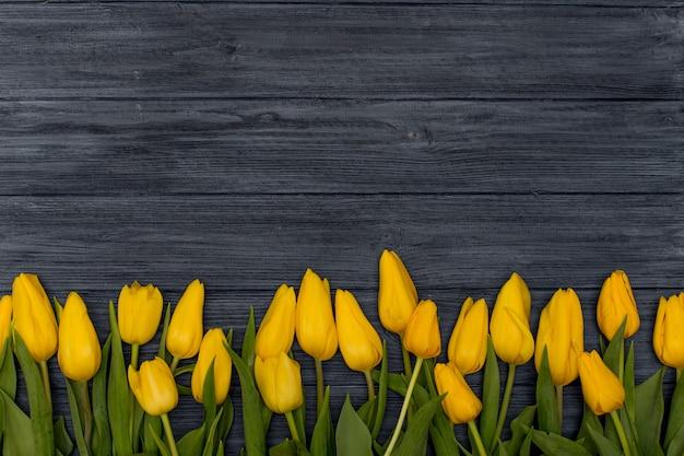 ヴィンテージドレスの木製の背景に黄色のチューリップ。チューリップと春の背景、テキスト用のスペースをコピーします。フラット横たわっていた、トップビュー。
