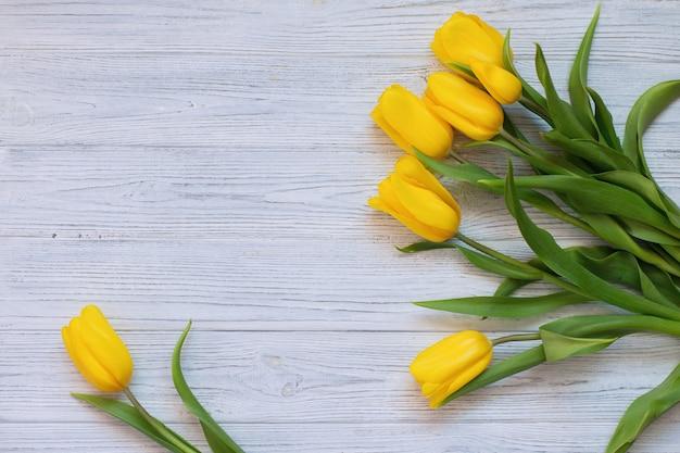 Тюльпаны весны желтые на белой деревянной предпосылке. копировать пространство плоская планировка, вид сверху.