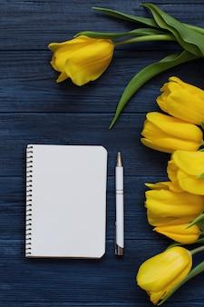Весенние желтые тюльпаны, пустой блокнот и ручка. плоская планировка, вид сверху.