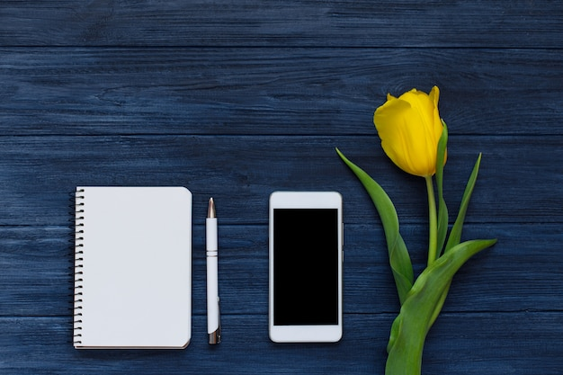 春の黄色いチューリップ、空白のノートブック、ペン、白いスマートフォン。フラット横たわっていた、トップビュー。