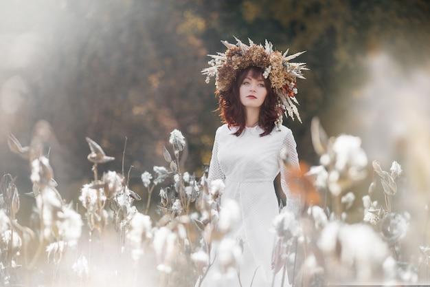 白いヴィンテージのドレスと秋のフィールドで頭の上のドライフラワーの花輪の美しい少女