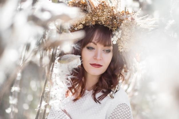 白いヴィンテージのドレスと風通しの良いふわふわの植物の中で頭の上のドライフラワーの秋の花輪で美しい少女の肖像画