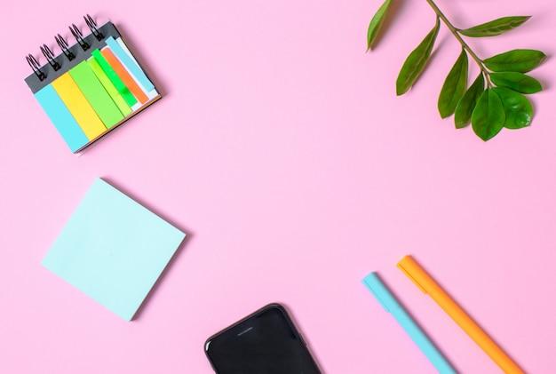 Розовый фон с блокнот, офисные очки, ручка, место для текста. концепция тренда.