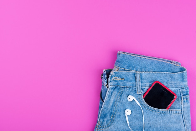 ブルージーンズ、後ろポケットにヘッドフォン付き携帯電話