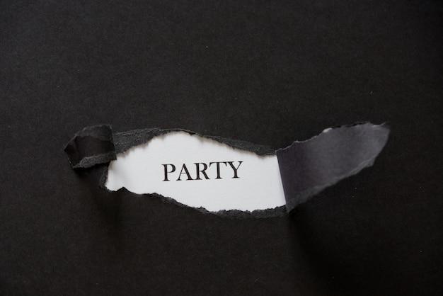 黒い破れた紙の後ろに印刷された単語パーティー