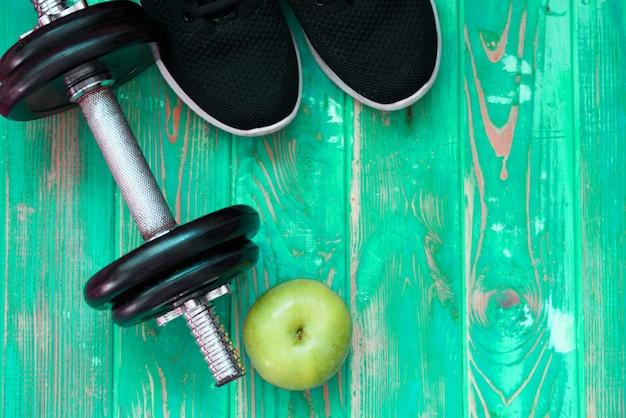 スポーツ用品-青リンゴ、水のボトル、ピンクのダンベルとミントの背景に黒いタオルのペア。