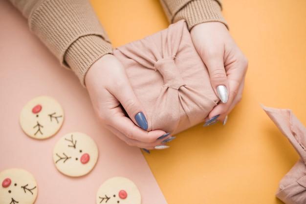 美しいマニキュアと女性の手でギフト。