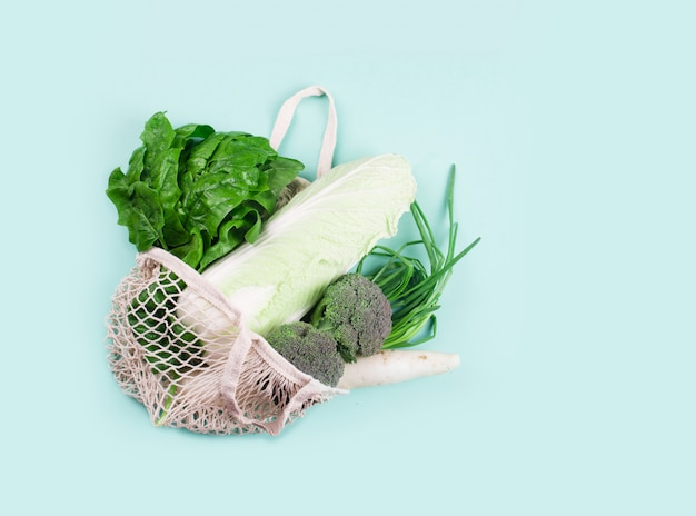 白い背景の上のブドウと環境に優しいベージュショッピングバッグ。フルーツ付きストリングバッグ。廃棄物ゼロ、プラスチックコンセプトなし。