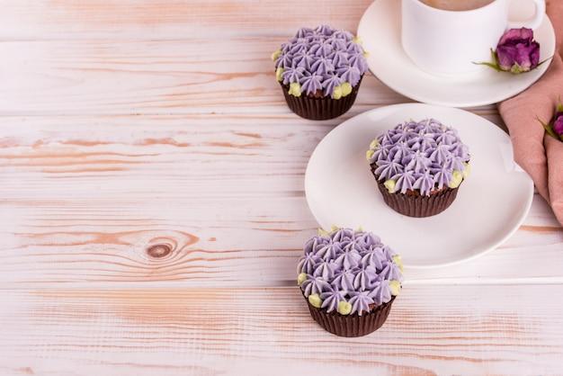 白い木製のテーブルにミルクとクリームと香り豊かなコーヒーとチョコレートのおいしいカップケーキ。