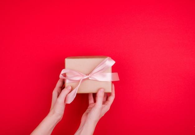 女性の手はクラフトラッパーの贈り物を持っており、真っ赤な背景にサテンのリボンが付いています。書く場所、上から見たところ。