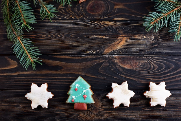 スプルースの小枝と木製の背景にクリスマスジンジャーブレッドクッキー
