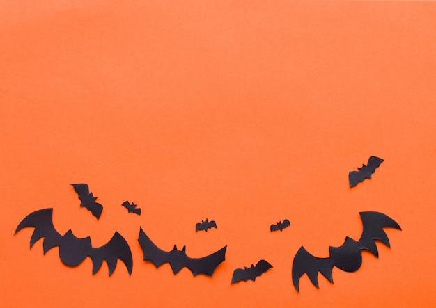 オレンジ色の背景にハロウィーンコウモリ