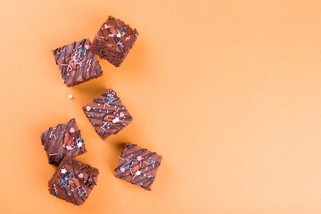 アーモンドナッツ、オレンジ色の背景にチョコレート艶出しとチョコレートのブラウニーデザート。