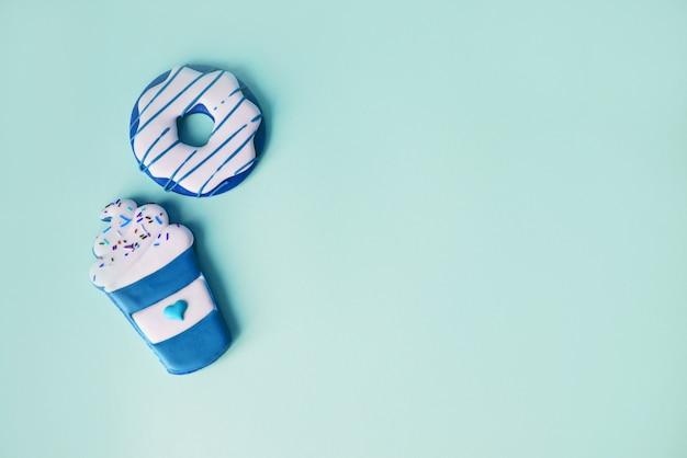 Пончики глазированные с окропляет на синем фоне.