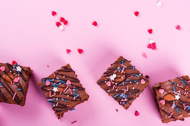 Шоколадный брауни десерт с миндалем внутри, праздничный порошок, на розовом фоне.