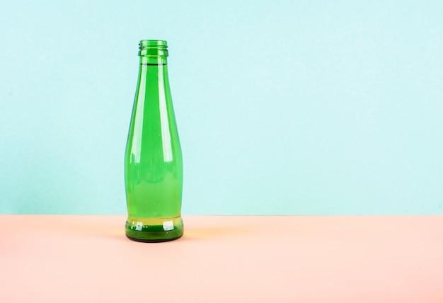 Стеклянная бутылка для воды ярко-зеленого цвета на светлом фоне.