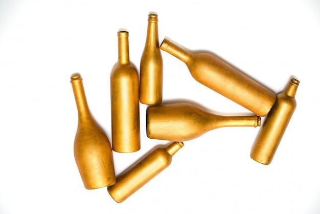 白で隔離されるゴールドカラーの異なるサイズのボトル
