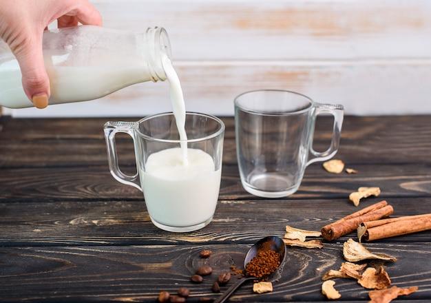 ガラスのカップ、シナモンスティック、干しキノコ、スプーンのフルフコーヒー入りの新鮮な牛乳