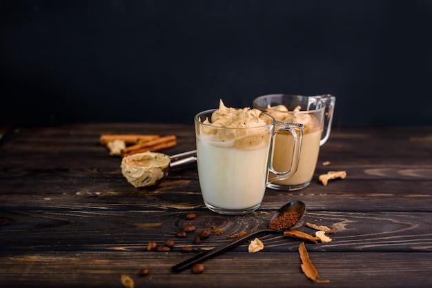 ガラスのカップ、シナモンスティック、干しキノコ、インスタントコーヒーのスプーン、砂糖入りの美味しくて香り高いダルゴナコーヒー。