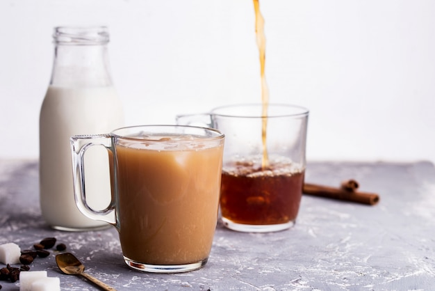 テーブルの上のミルク、シナモンスティック、コーヒー豆、砂糖、スプーンで冷やしたコーヒー。
