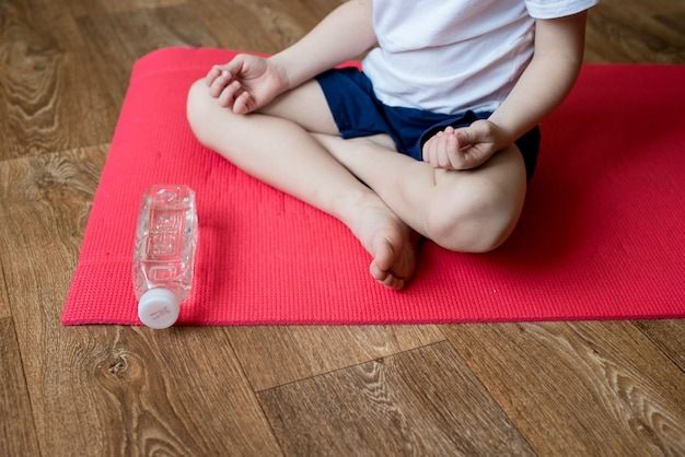 少年はピンクのマットの上に座ってヨガをします。自宅で検疫するのに間に合うスポーツ。