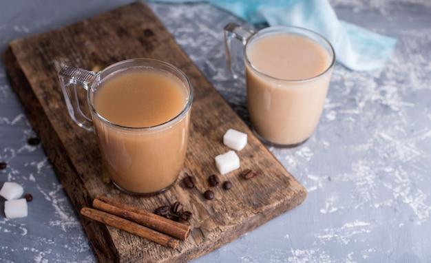 Кофе охлажденный с молоком, палочки корицы, кофе в зернах, сахар, ложка на столе.