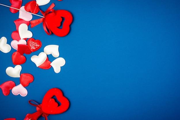 美しい青色の背景にバレンタインデーの赤いハート。ハートペンダント。