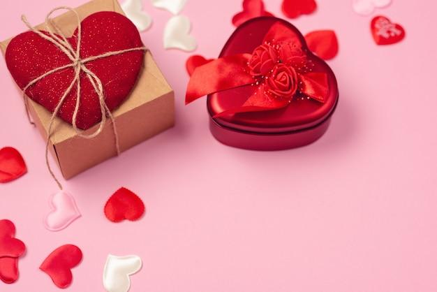 美しいピンクの背景にバレンタインデーへの贈り物と赤いハート。ハートペンダント。