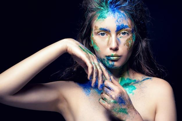 Красивое лицо с цветной краской на черном, красивая девушка, красочный макияж, модная женщина, тонированное изображение,