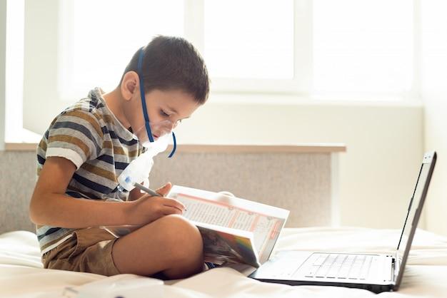 子供は、噴霧器、ラップトップ、および本を備えた酸素マスクで家庭のレッスンを学びます