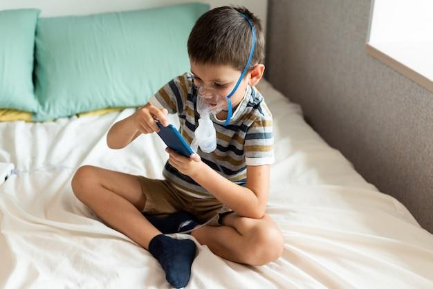 噴霧器を備えた酸素マスクの子供がスマートフォンで遊ぶ