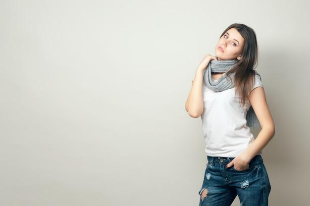 Портрет молодой девушки в белой рубашке и джинсах
