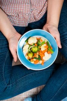 Руки держат тарелку овощей