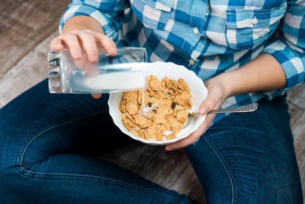 Девушка с тарелкой из цельного зерна злаков и молока