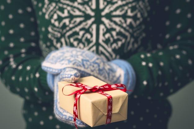 Девушка в новогоднем свитере держит подарок. подарки для мужчин. с рождеством. подарок девушке. свитер с рождественским украшением. вязанное платье.