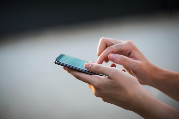 テキストメッセージまたはプロモーションコンテンツの空白の画面を持つ携帯電話を保持している女性の手のクローズアップ