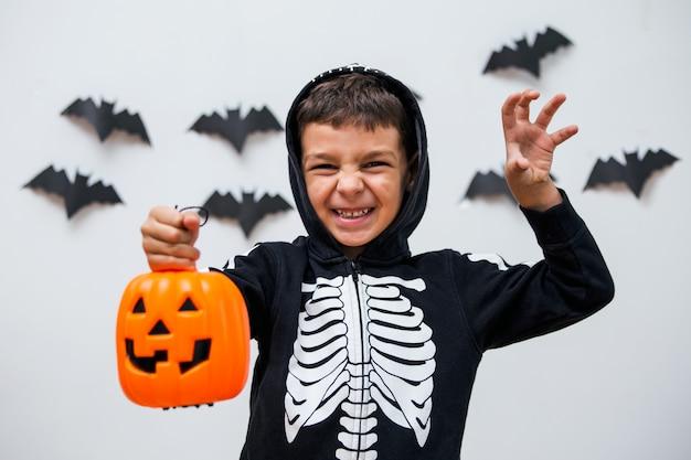 ポーズを怖がらせるハロウィーンの衣装でかわいい子供。