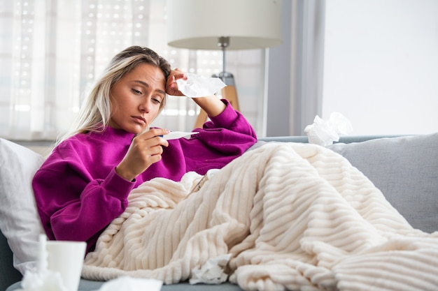 Больная женщина, лежа в постели с высокой температурой. простуда и мигрень.