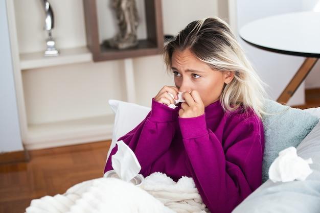Женщина простудилась и грипп чихает в ткани.