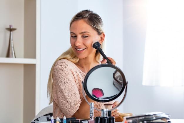 彼女をやっている若い美しい女性が鏡の近くを構成します。