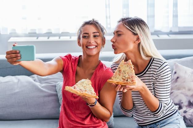 自宅のソファーでワインとピザを食べる女性の友人