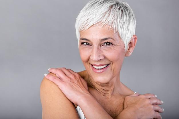 カメラを見て笑顔の年配の女性の肖像画。灰色の背景に分離されたスパでのトリートメント後の成熟した女性の顔をクローズアップ。アンチエイジングのコンセプト。