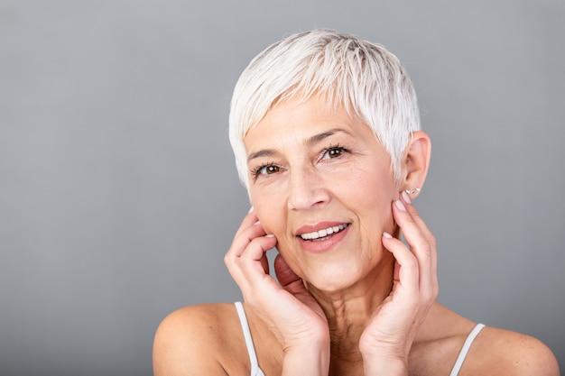 彼女の完璧な肌に触れるとカメラ目線の美しい年配の女性の肖像画。灰色の背景に分離された顔をマッサージしわと成熟した女性の顔をクローズアップ。老化プロセスの概念。