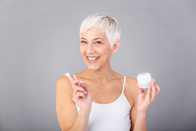 Красивая зрелая женщина, держа банку крема для кожи лица и тела, изолированные на сером фоне. счастливая старшая женщина прикладывая против старения увлажняющий крем и смотря камеру. косметическая антивозрастная процедура.